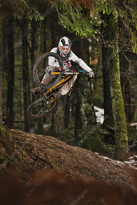 Mountain biker jumping muddy forest track
