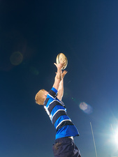 Rugby player reaching to catch ball