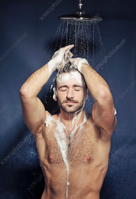 Young man shampooing hair under shower