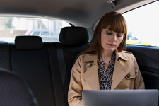 Business woman with laptop in car