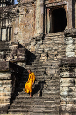 Young Buddhist monk walking down steps at temple, Cambodia