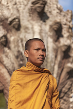 Young Buddhist monk standing outside temple, close up