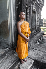 Young buddhist monk standing outside temple, Cambodia