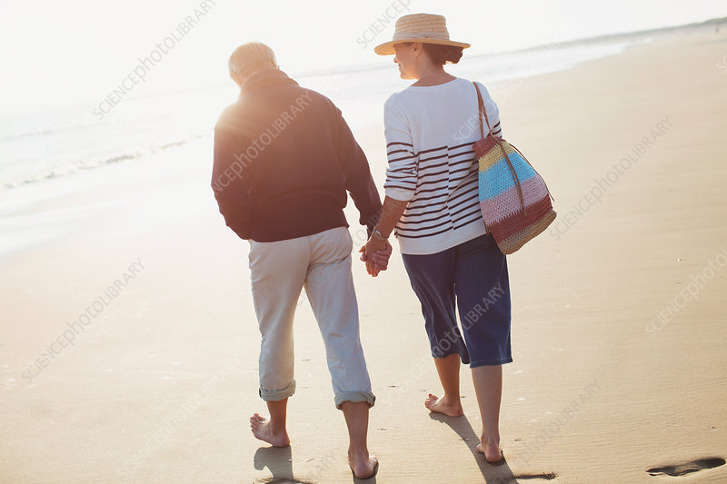 Barefoot mature couple holding hands and walking