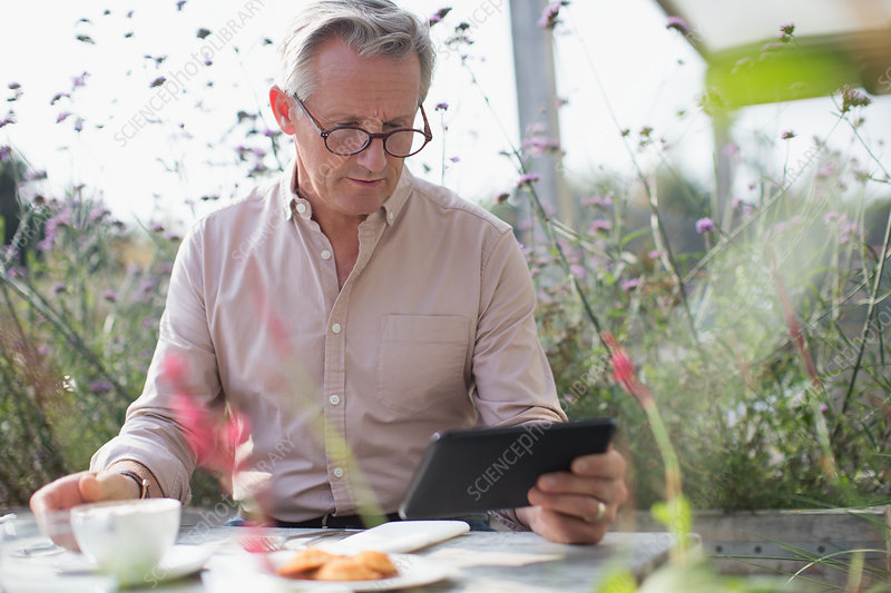 Senior man using tablet and drinking coffee