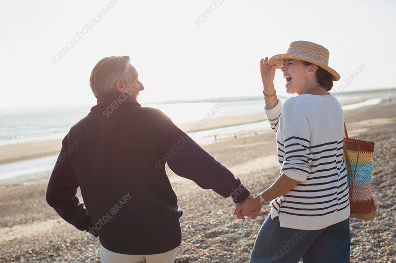 Laughing mature couple holding hands and walking