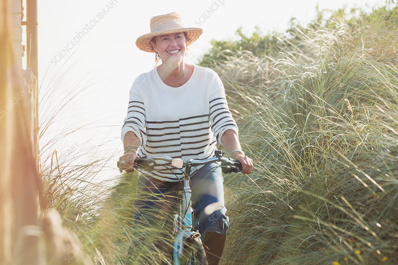 Smiling mature woman riding bicycle