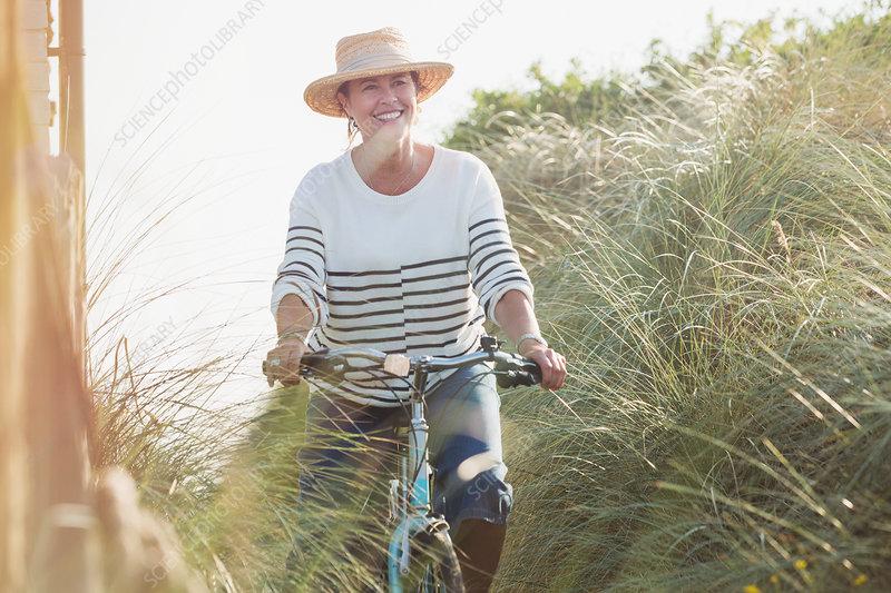 Smiling mature woman riding bicycle