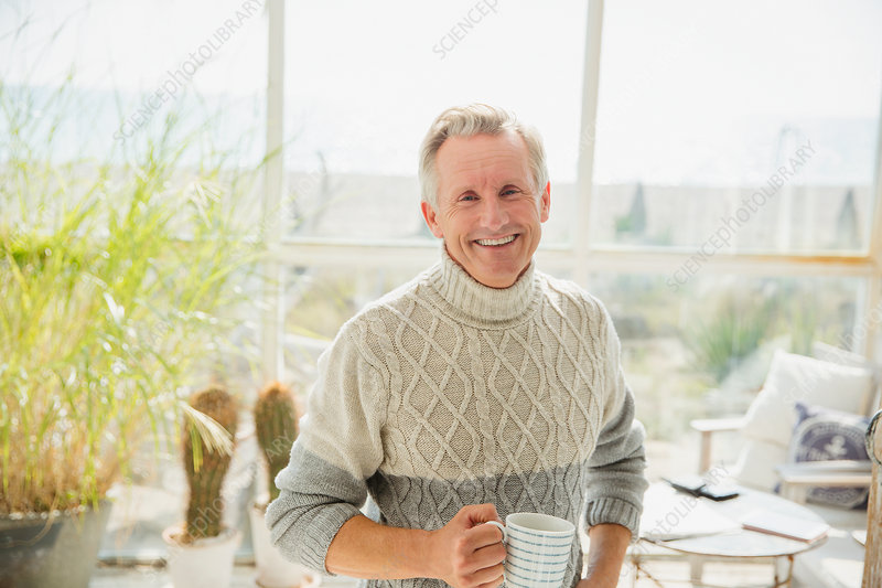 Senior man drinking coffee in sunny porch