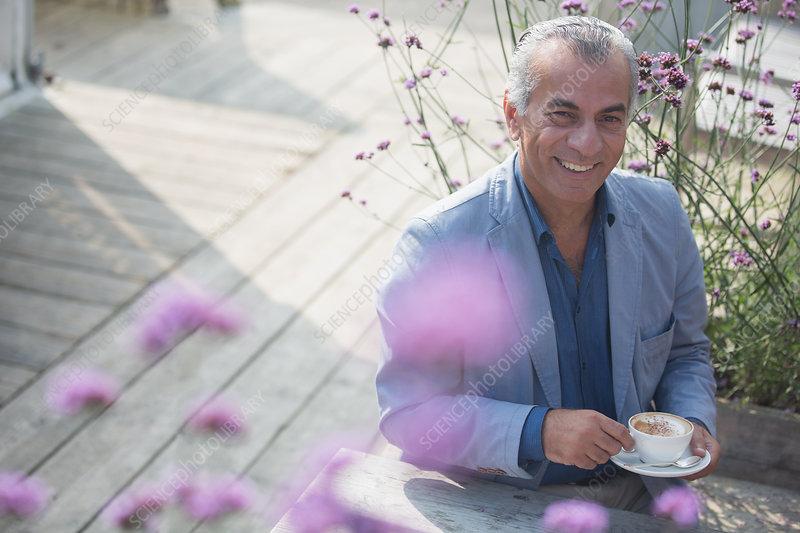 Portrait senior man drinking coffee on sunny patio