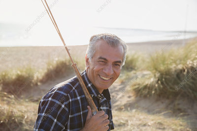 Portrait senior man with fishing rod walking