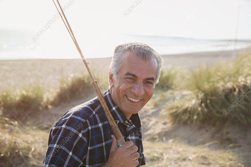 Portrait senior man with fishing rod walking