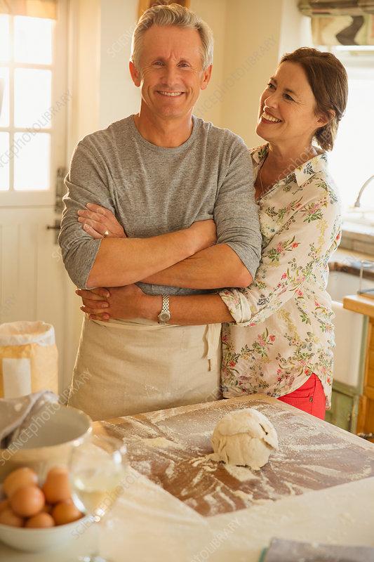 Smiling couple hugging, baking in kitchen