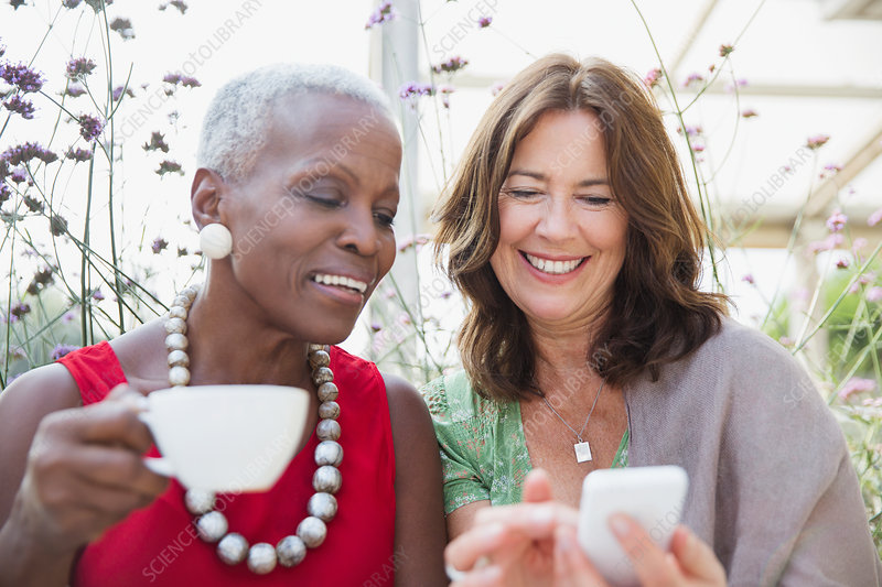 Smiling mature women friends drinking coffee