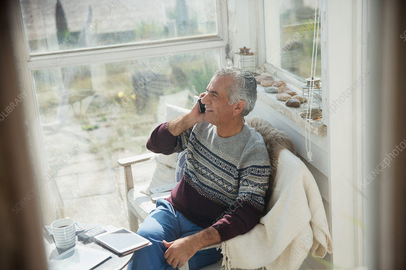 Senior man talking on cell phone on sun porch