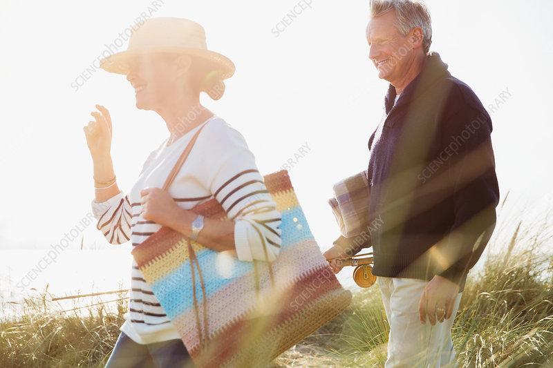 Mature couple walking in sunny beach grass