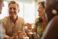 Laughing mature couple drinking wine table