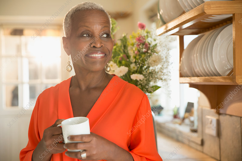 Smiling senior woman drinking coffee in kitchen