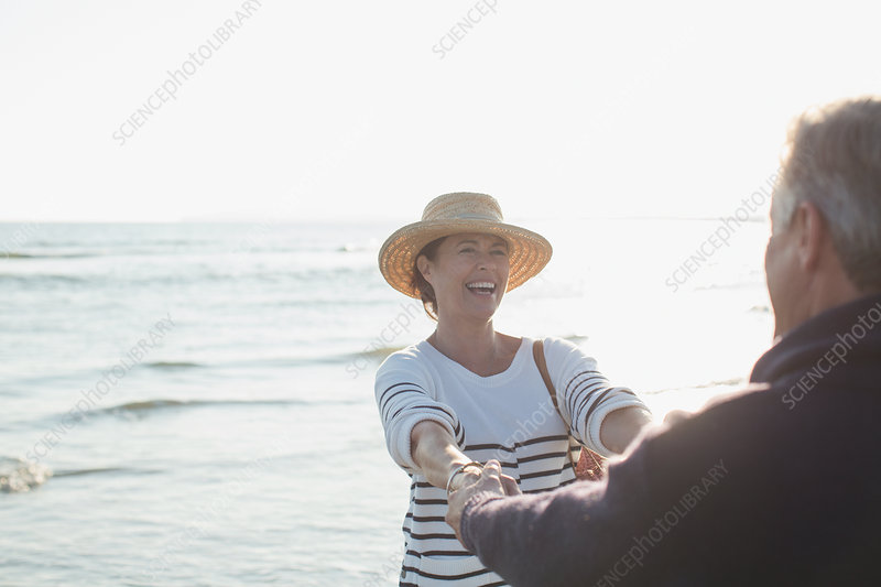 Mature couple holding hands on sunny ocean beach