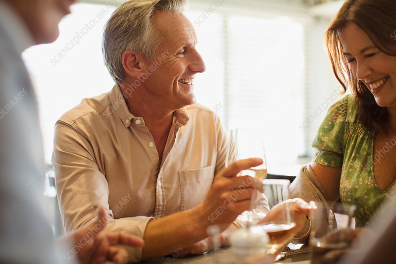 Smiling mature couple drinking wine, dining table