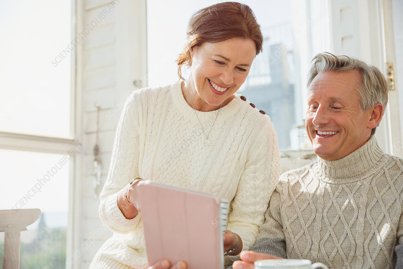 Smiling mature couple using tablet on sunny porch