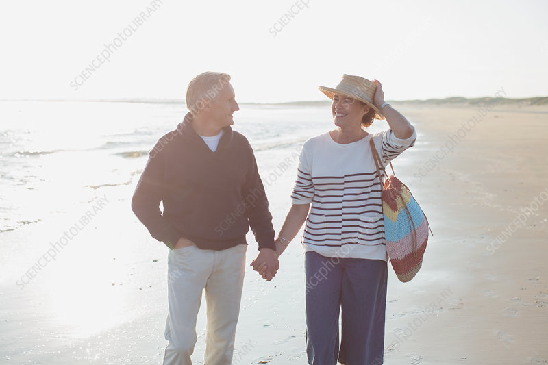Smiling mature couple holding hands and walking