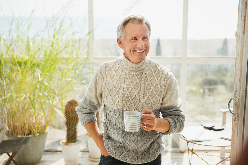 Smiling mature man drinking coffee house sun porch