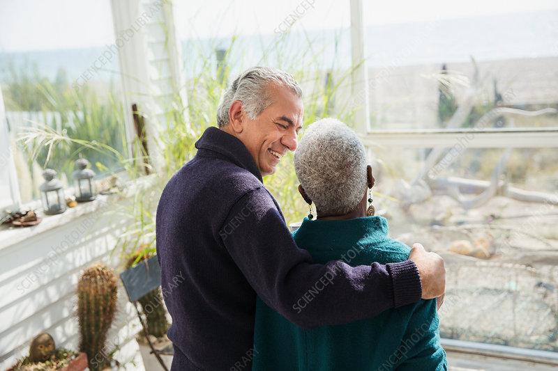 Senior couple hugging house sun porch