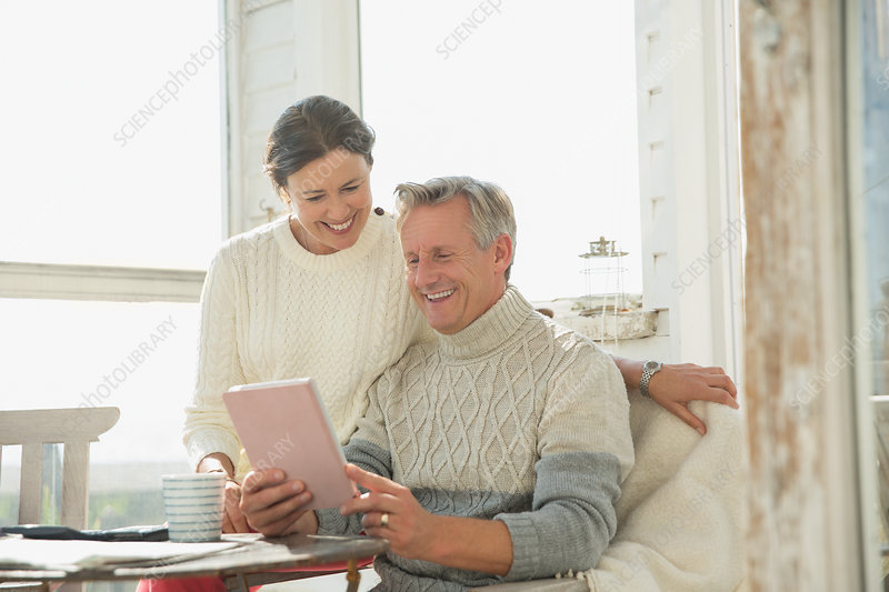 Smiling mature couple using tablet