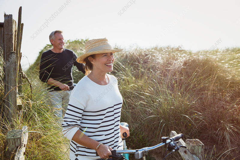 Mature couple walking bicycles