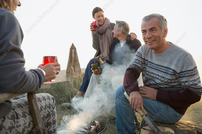 Mature couples drinking wine and barbecuing