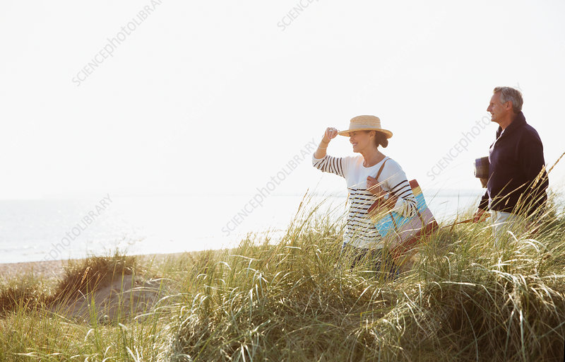 Mature couple walking in sunny beach grass
