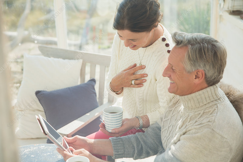 Mature couple using tablet on porch