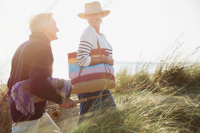 Smiling mature couple with fishing rod walking