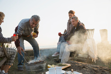 Mature couples barbecuing and drinking wine