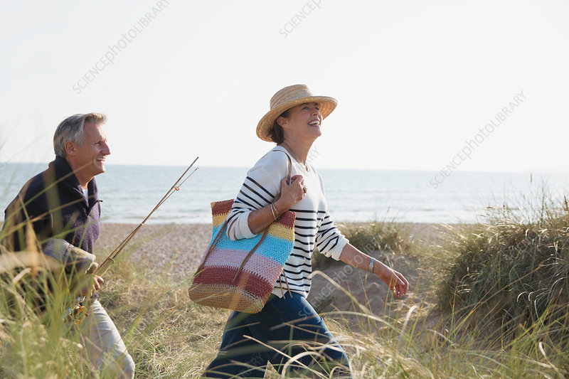 Mature couple with fishing rod walking