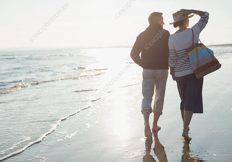 Mature couple walking on sunny ocean beach