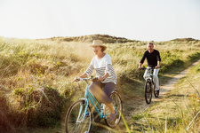 Playful mature couple riding bicycles grass path