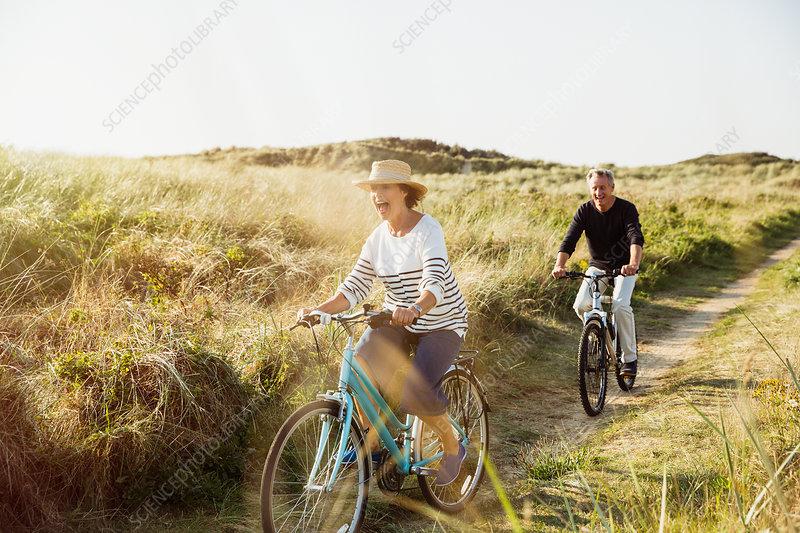 Playful mature couple riding bicycles grass path