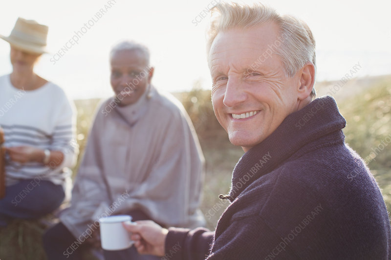 Portrait senior man drinking coffee with friends