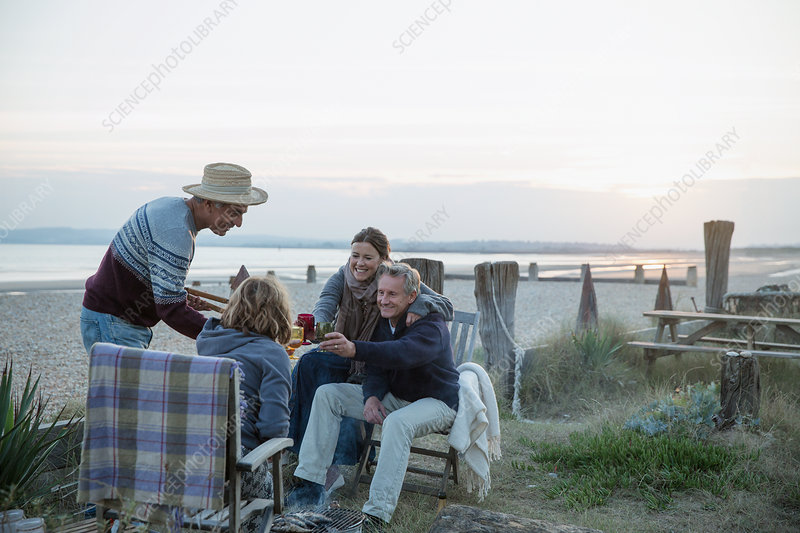 Mature couples barbecuing, drinking wine