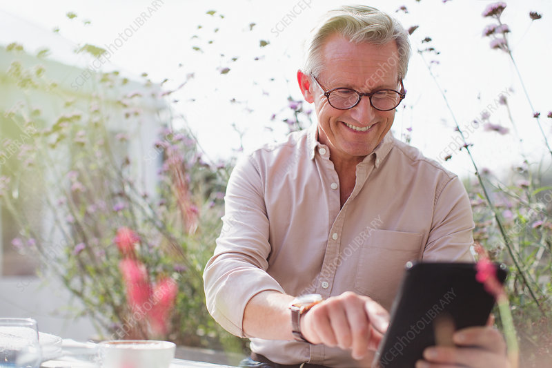 Smiling senior man using digital tablet on patio