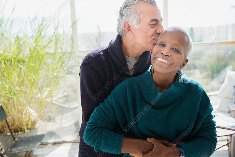 Portrait senior couple hugging and kissing