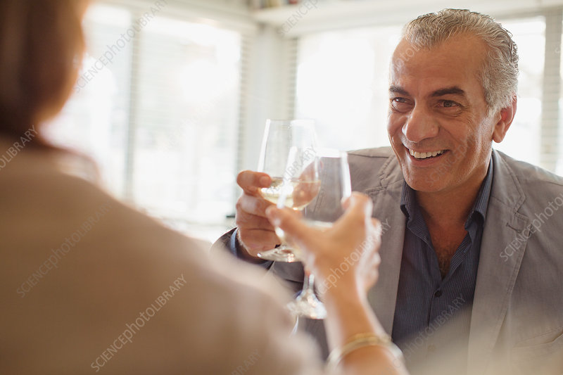 Senior man toasting wine glasses with woman