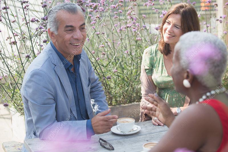 Senior friends drinking coffee on patio