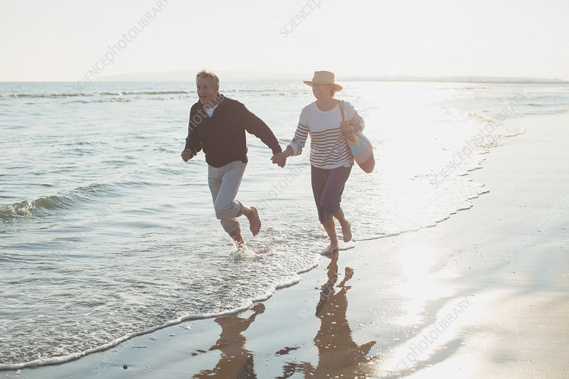 Playful mature couple holding hands and running