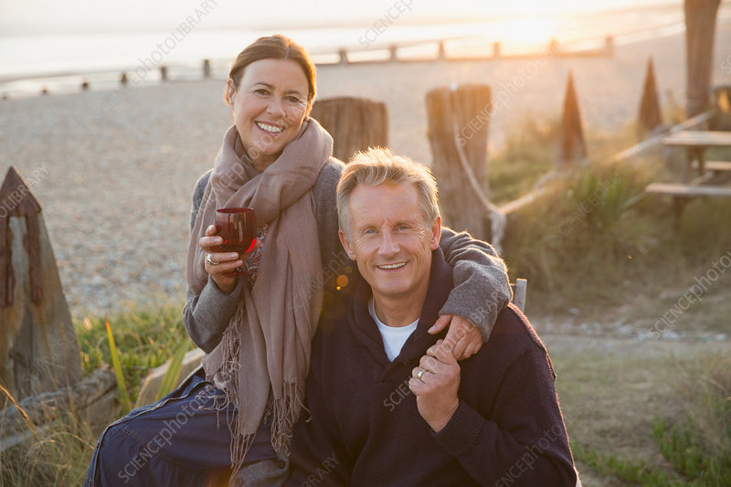 Mature couple holding hands and drinking wine