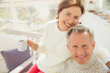 Portrait mature couple hugging and drinking coffee