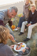 Mature couples barbecuing on beach