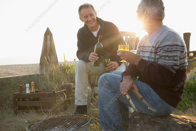 Senior men drinking wine and barbecuing